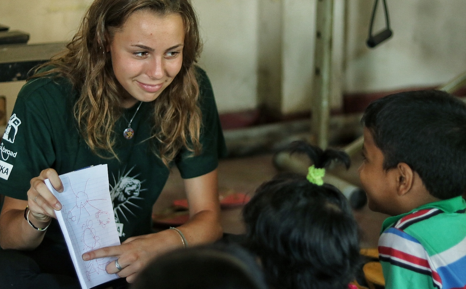 A student volunteering overseas for her transition year teaches English to Sri Lankan children.